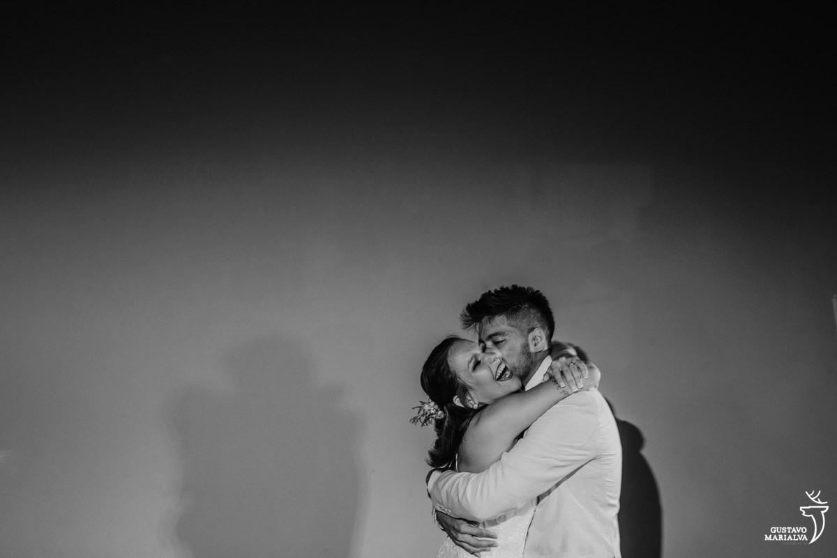 noivos fazem a primeira dança, abraçados e sorrindo no Uniq Beach Lounge em Búzios