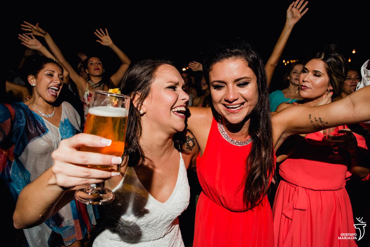 noiva com copo de cerveja na mão abraça a madrinha emocionada enquanto convidados dançam no fundo