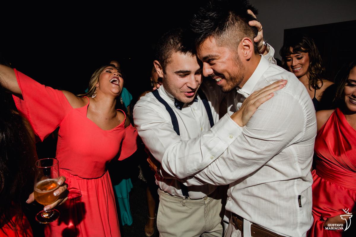 noivo e padrinho se abraçam enquanto madrinha dança na festa de casamento no Uniq Beach Lounge em Búzios