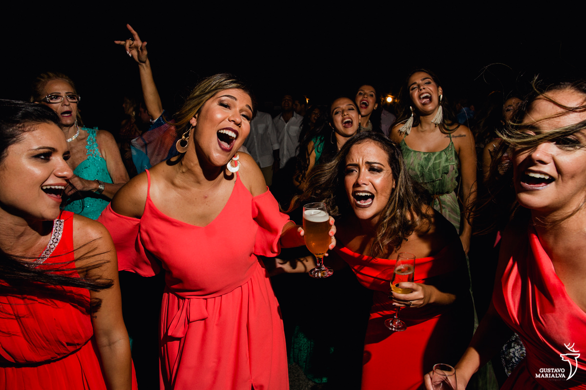 Madrinha com copo de cerveja na mão dança acompanhada de outras amigas na festa de casamento no Uniq Beach Lounge em Búzios