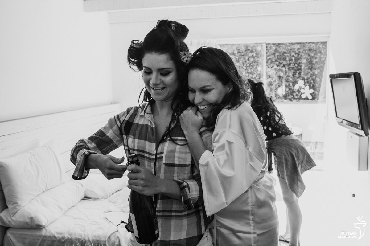 madrinha abre a garrafa de espumante e a noiva a abraça sorridente durante o making of do casamento na Serana Boutique Resort em Búzios
