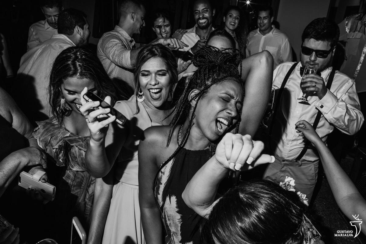 Convidadas dançam funk com a mão na cabeça enquanto padrinho de óculos escuros toma um drink no Uniq Beach Lounge em Búzios
