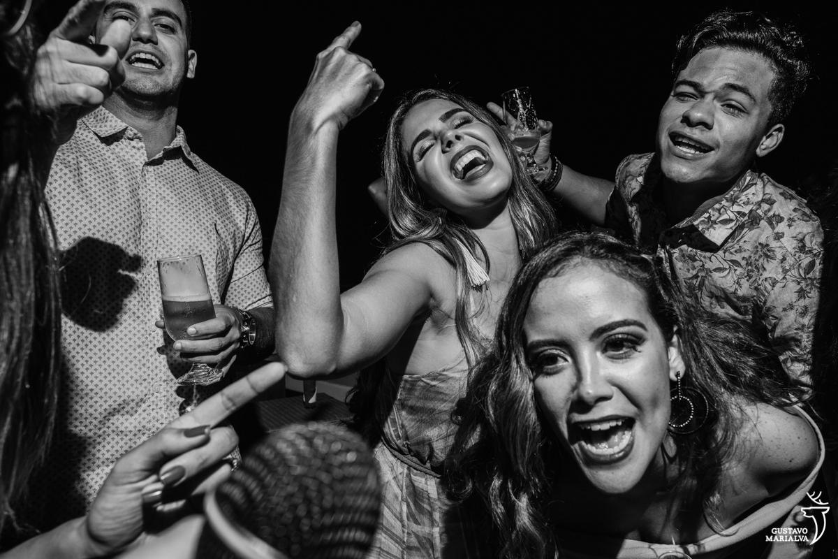 convidadas animadas e sorrindo cantam no microfone no Uniq Beach Lounge em Búzios