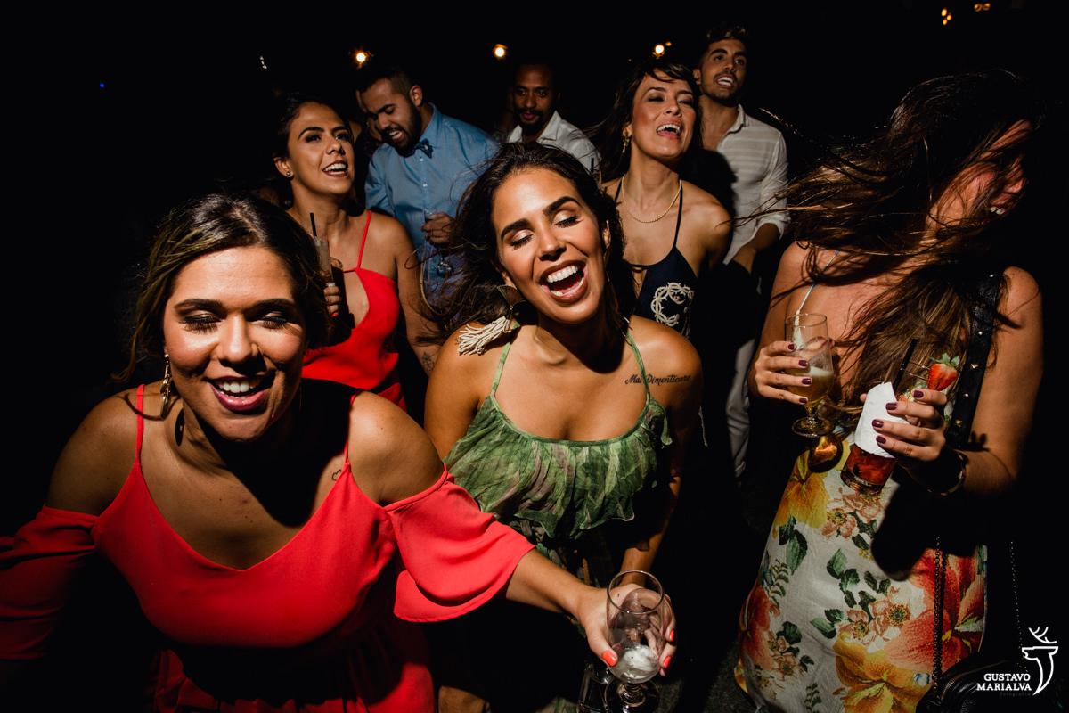 convidadas sorridentes dançam na festa de casamento no Uniq Beach Lounge em Búzios