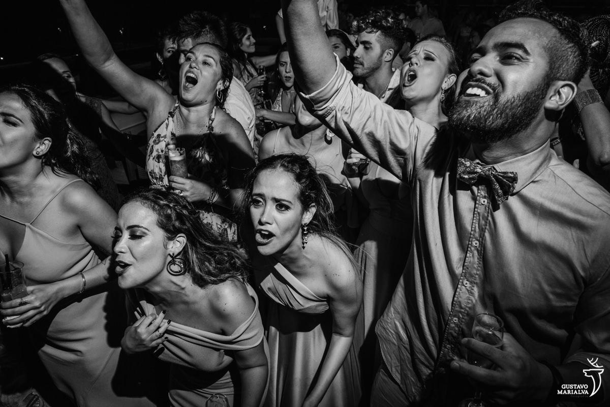 amigos e convidados dançam animados e cantam na festa de casamento no Uniq Beach Lounge em Búzios