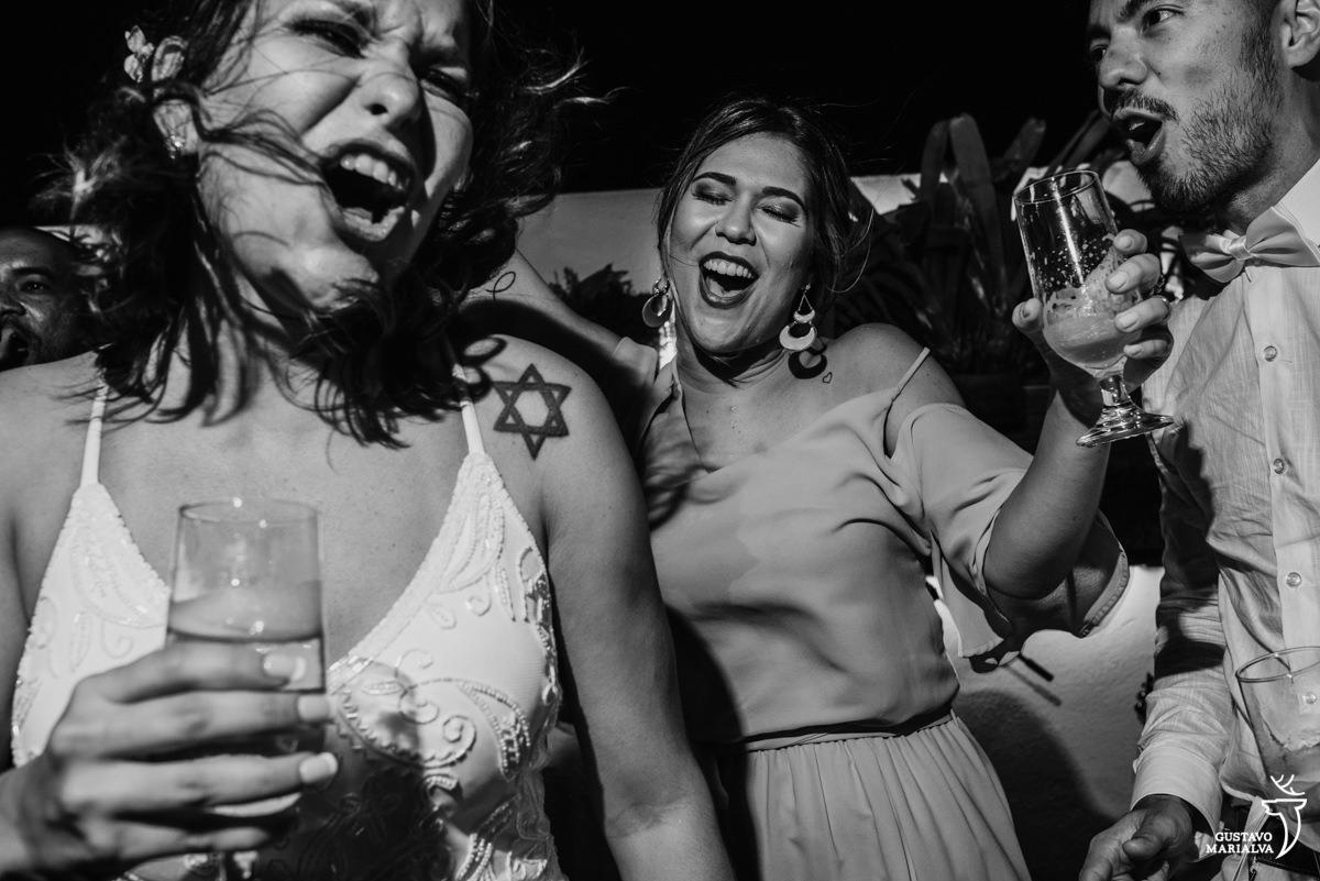 noivos com copo na mão dançam e cantam em cima do palco acompanhados de uma madrinha na festa de casamento no Uniq Beach Lounge em Búzios