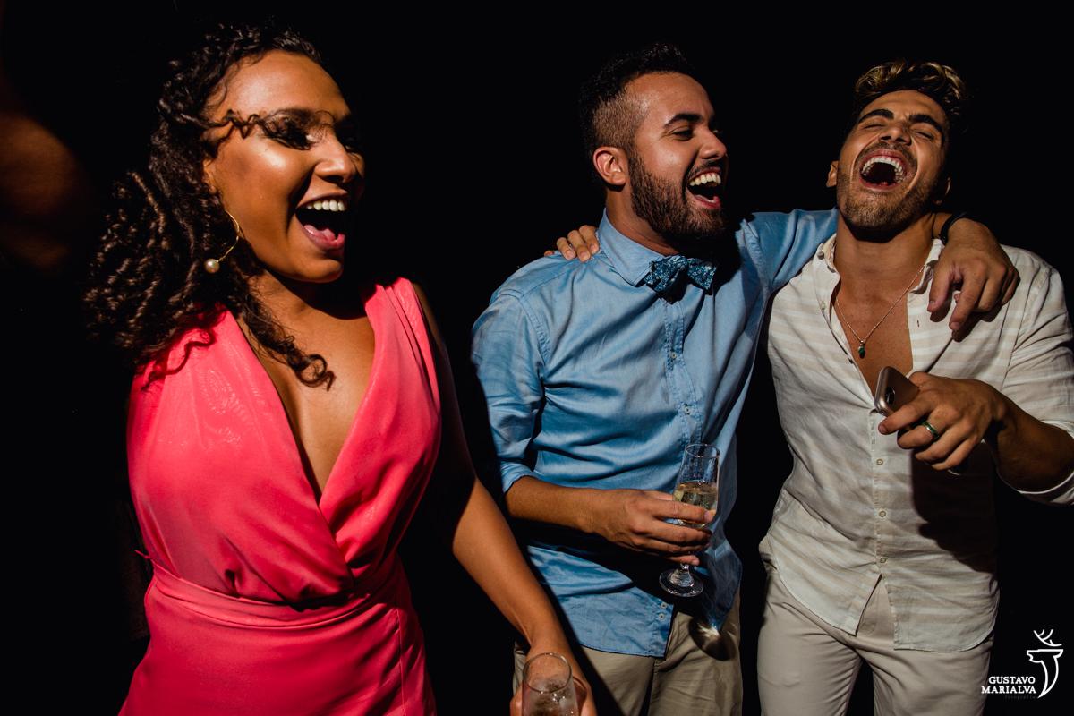 casal de namorados gay dançam animados e abraçados enquanto madrinha dança ao lado na festa de casamento no Uniq Beach Lounge em Búzios