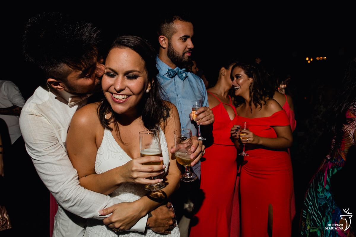 noivo abraça noiva por trás e dá um beijo enquanto madrinhas conversam sorrindo ao fundo no Uniq Beach Lounge em Búzios