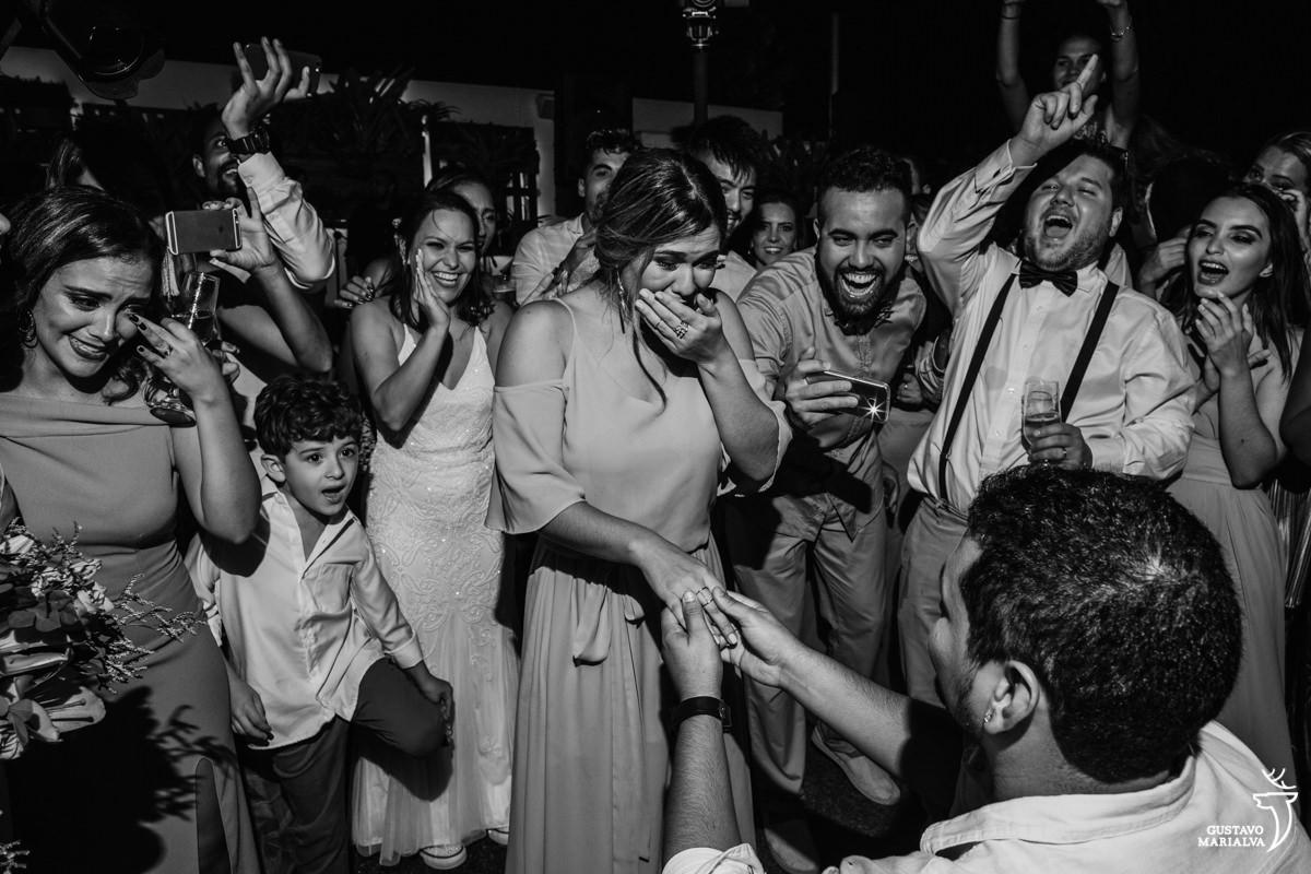 madrinha chora muito com o pedido de casamento surpresa do namorado enquanto noiva emocionada abraça as amigas que choram