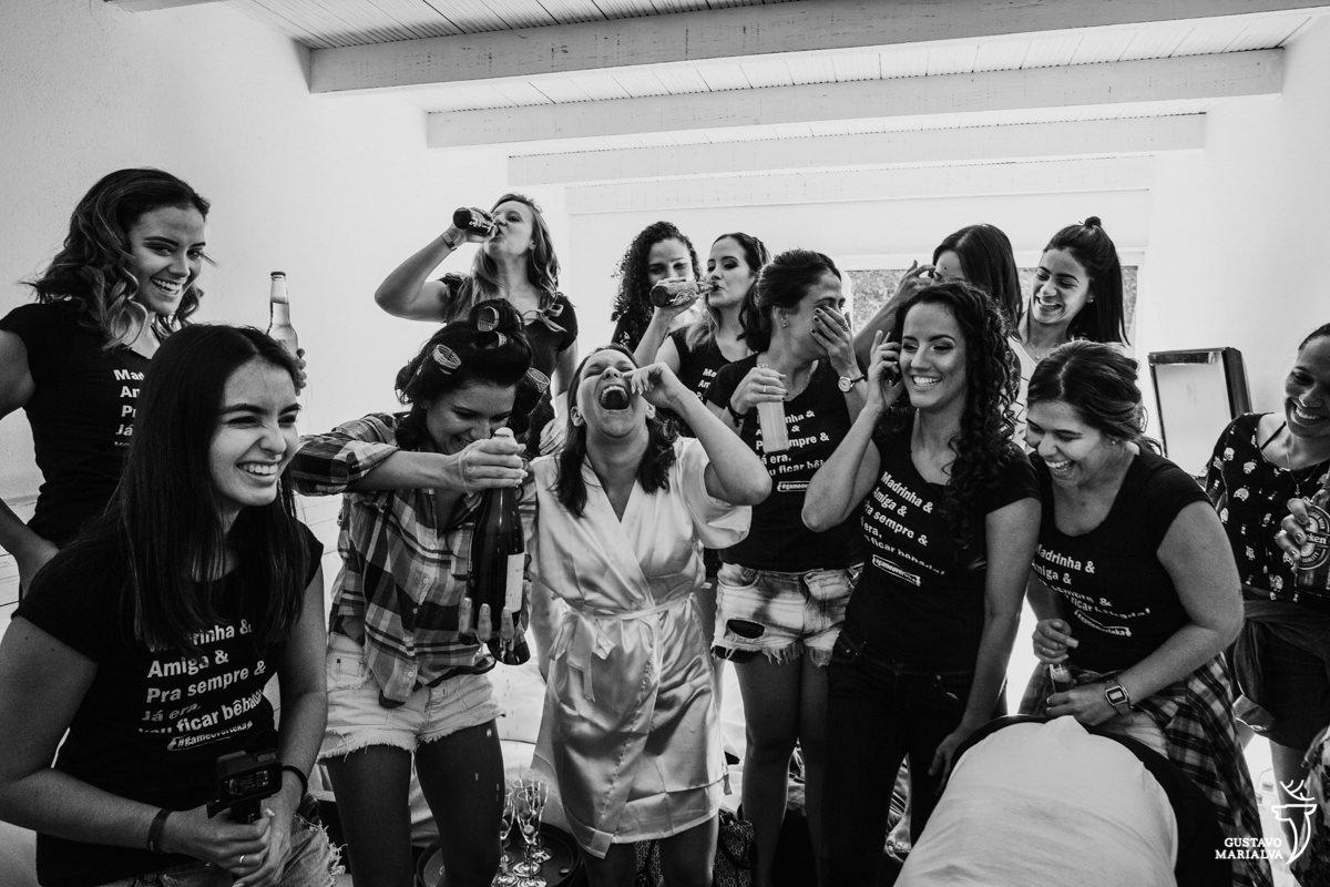 madrinhas estouram o espumante, enquanto noiva ri, e outras madrinhas tomam cerveja no gargalo da garrada na Serana Boutique Resort em Búzios