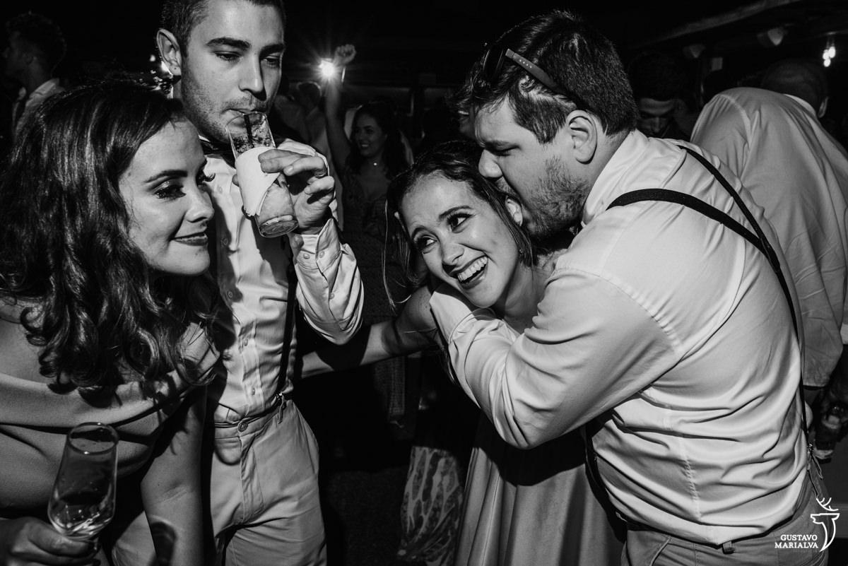 padrinho morde a orelha da madrinha enquanto amigo toma um drink e outra madrinha dança sorrindo