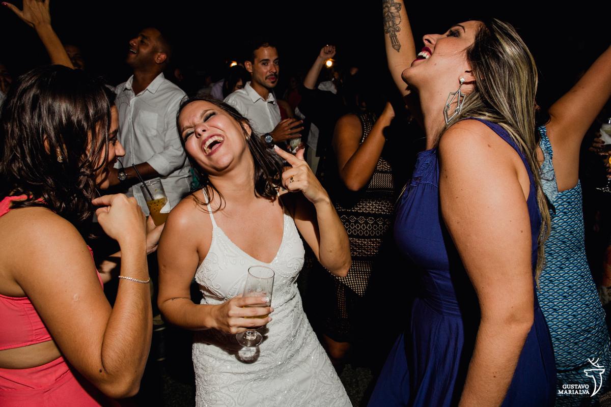 noiva sorrindo com copo na mão dança com as amigas na festa de casamento no Uniq Beach Lounge em Búzios