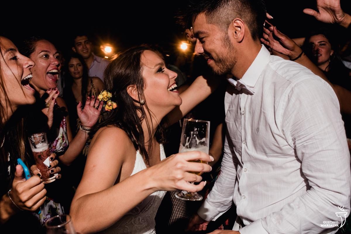 noiva com copo na mão dança com noivo enquanto amigos vibram no fundo