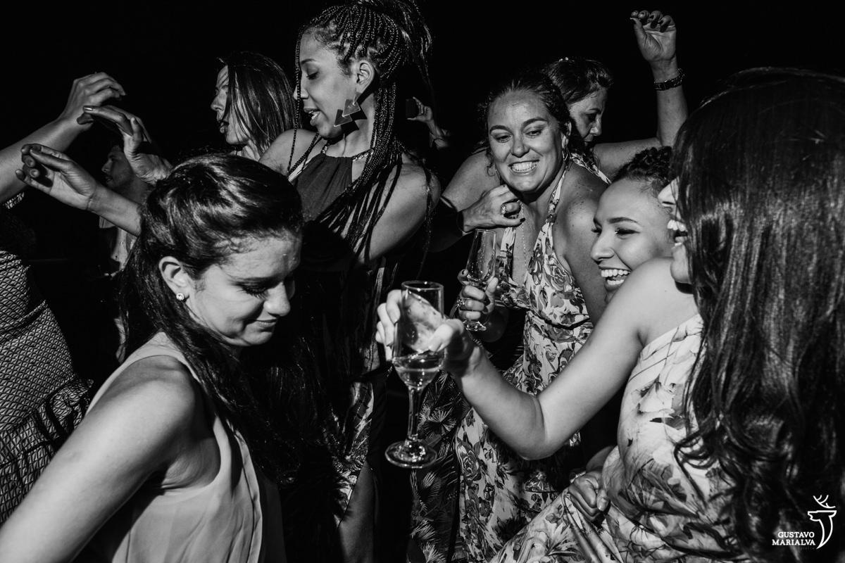 amigas dançam funk com taça de espumante na mão no Uniq Beach Lounge em Búzios