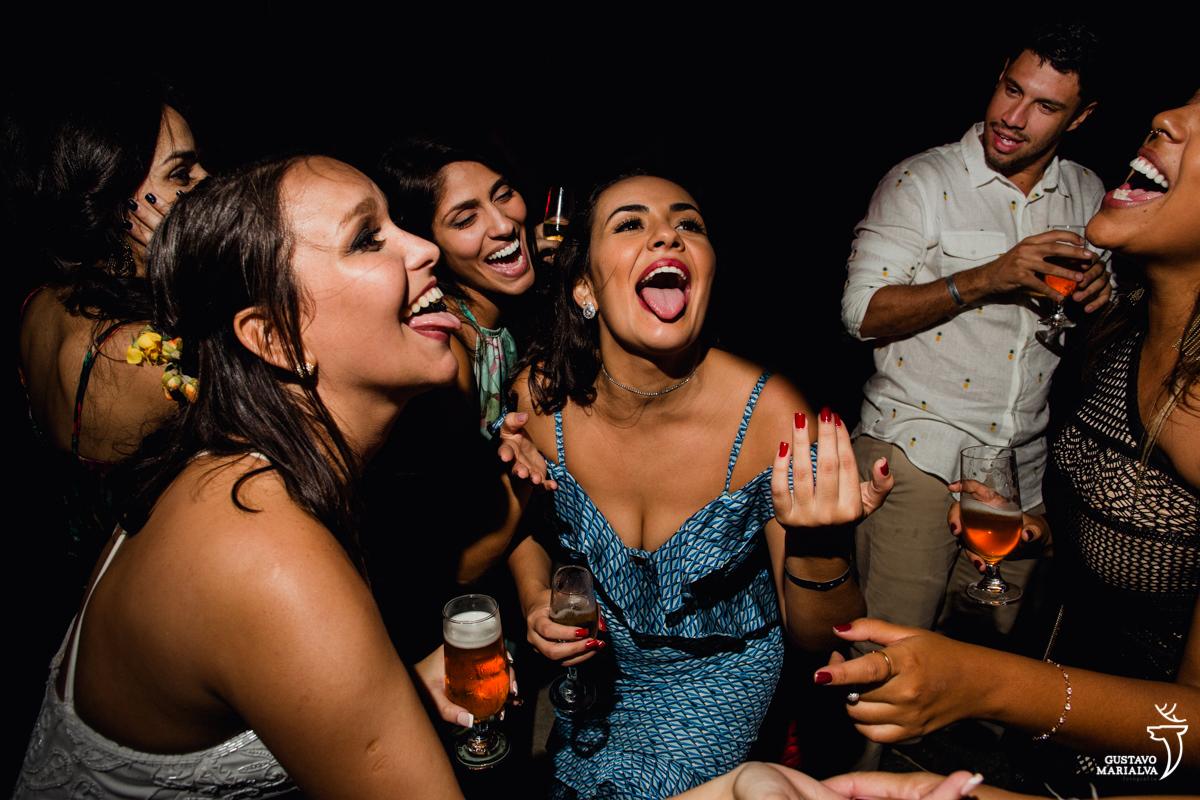 noiva e amiga dançam com a língua para fora e convidado sorri ao fundo