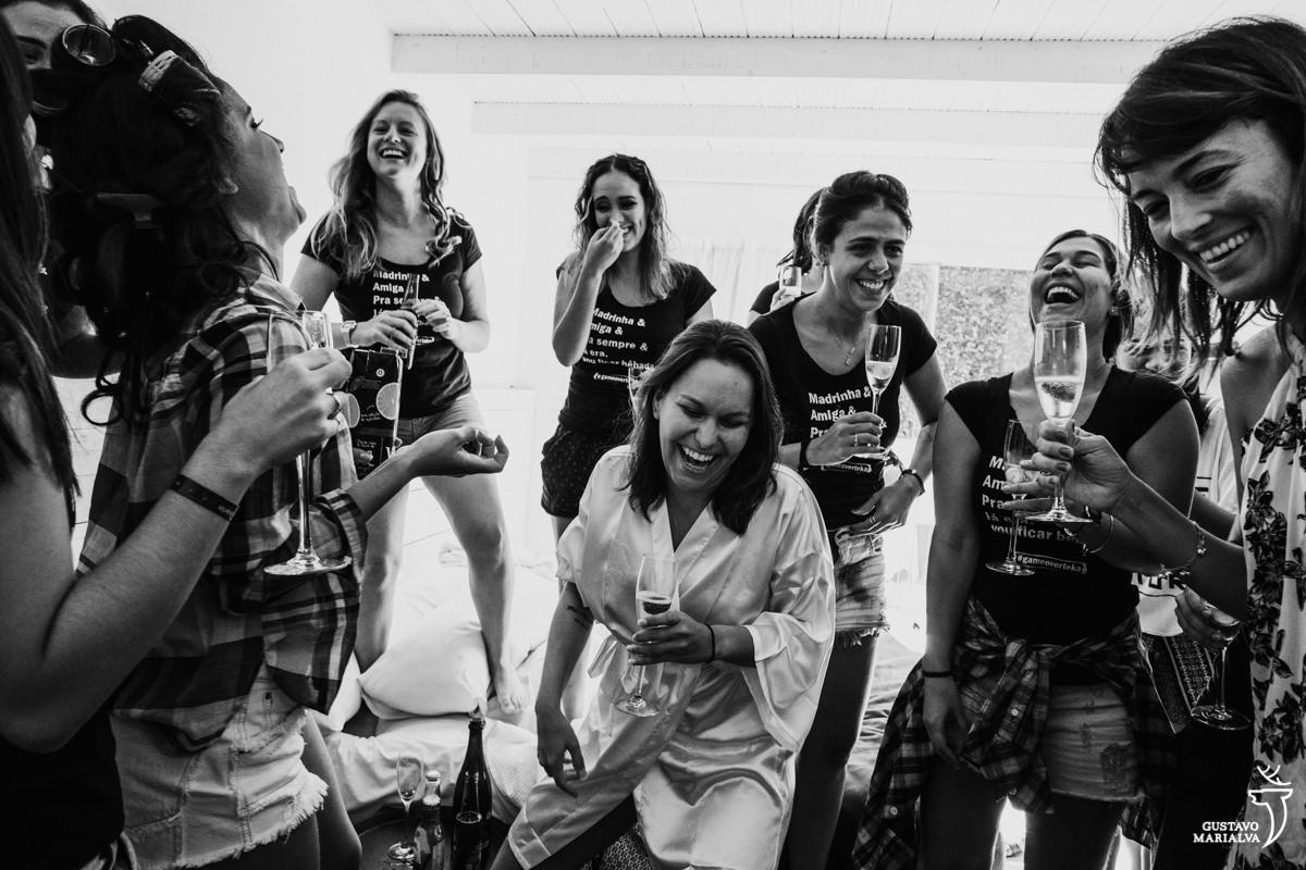 madrinhas e noivas com a taça de espumante nas mãos rindo e brincando na Serana Boutique Resort em Búzios