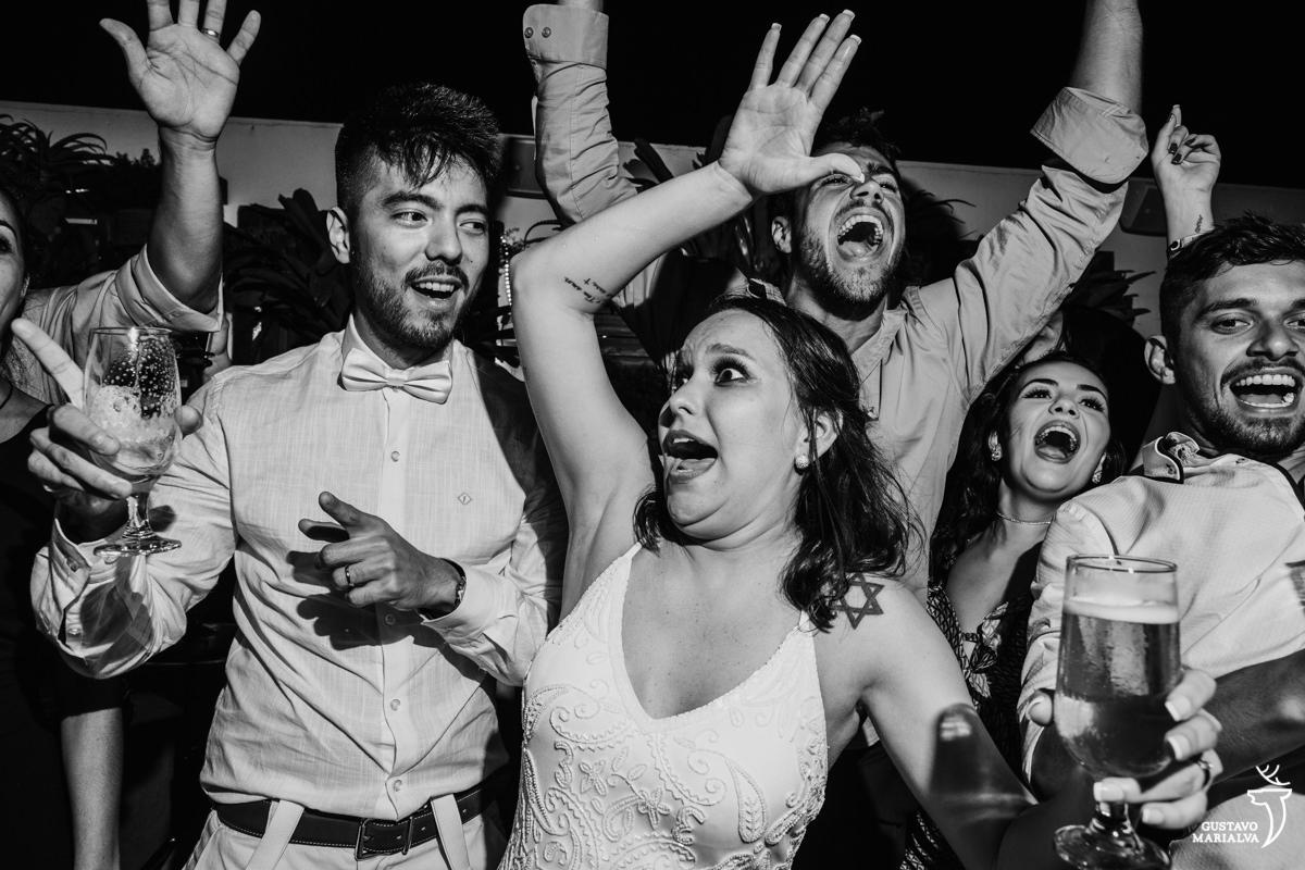 noiva faz careta com noivo e convidados gritam e dançam ao fundo no Uniq Beach Lounge em Búzios