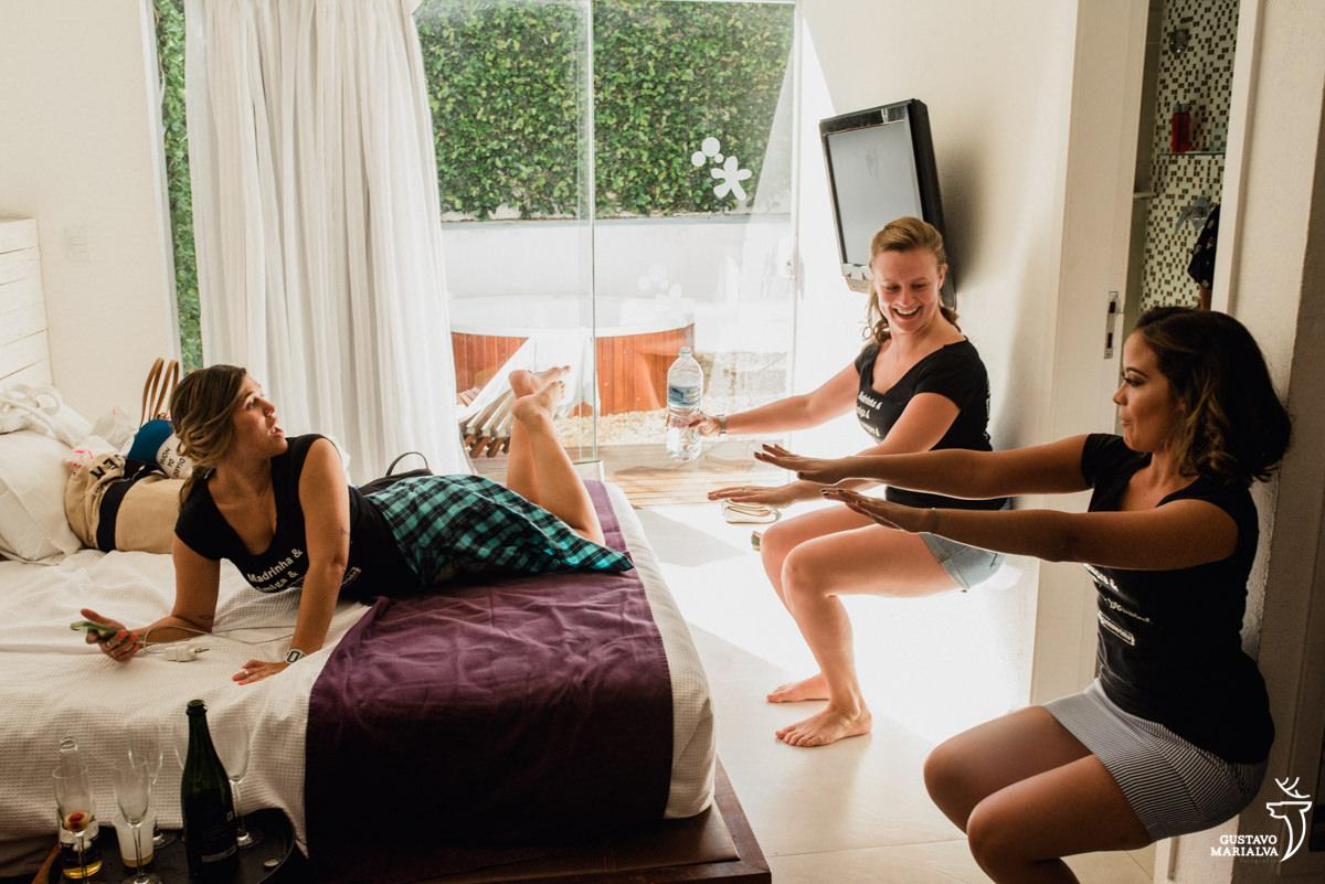 madrinhas fazem agachamento na parede enquanto outra madrinha ri deitada na cama na Serana Boutique Resort em Búzios