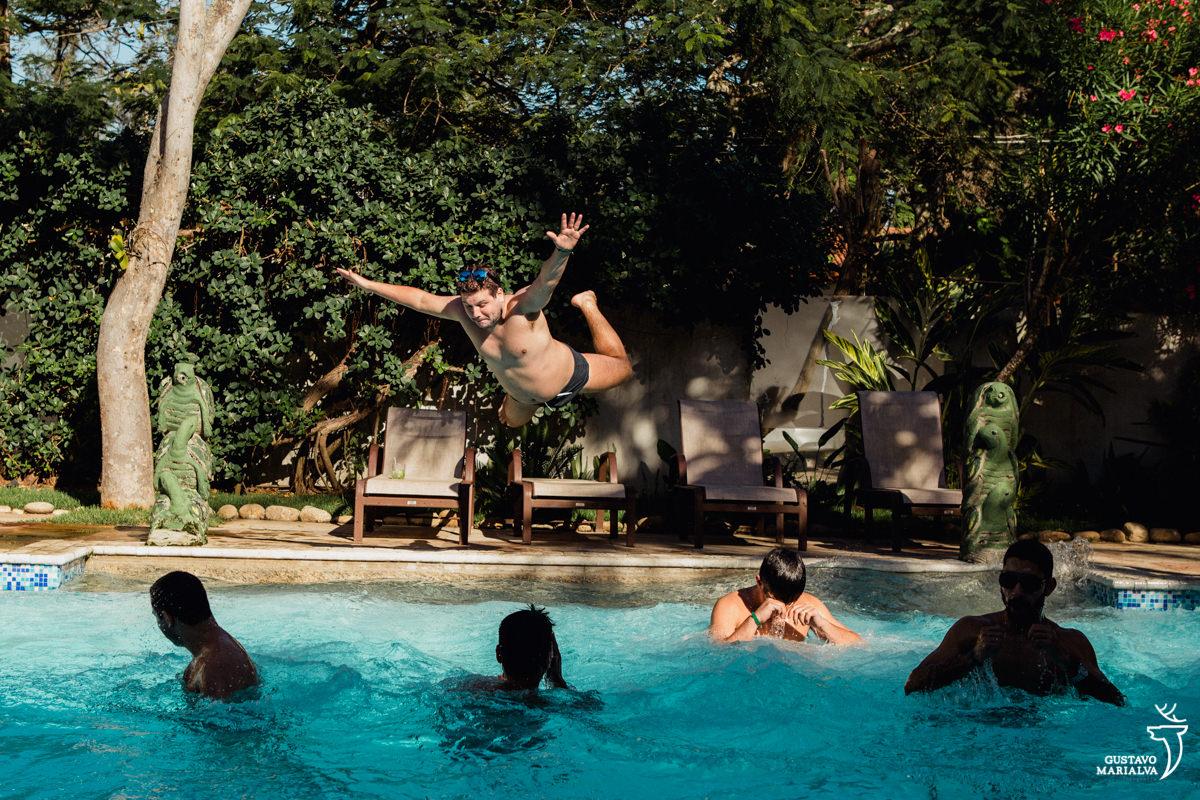 padrinhos na piscina enquanto amigo pula de barriga na piscina