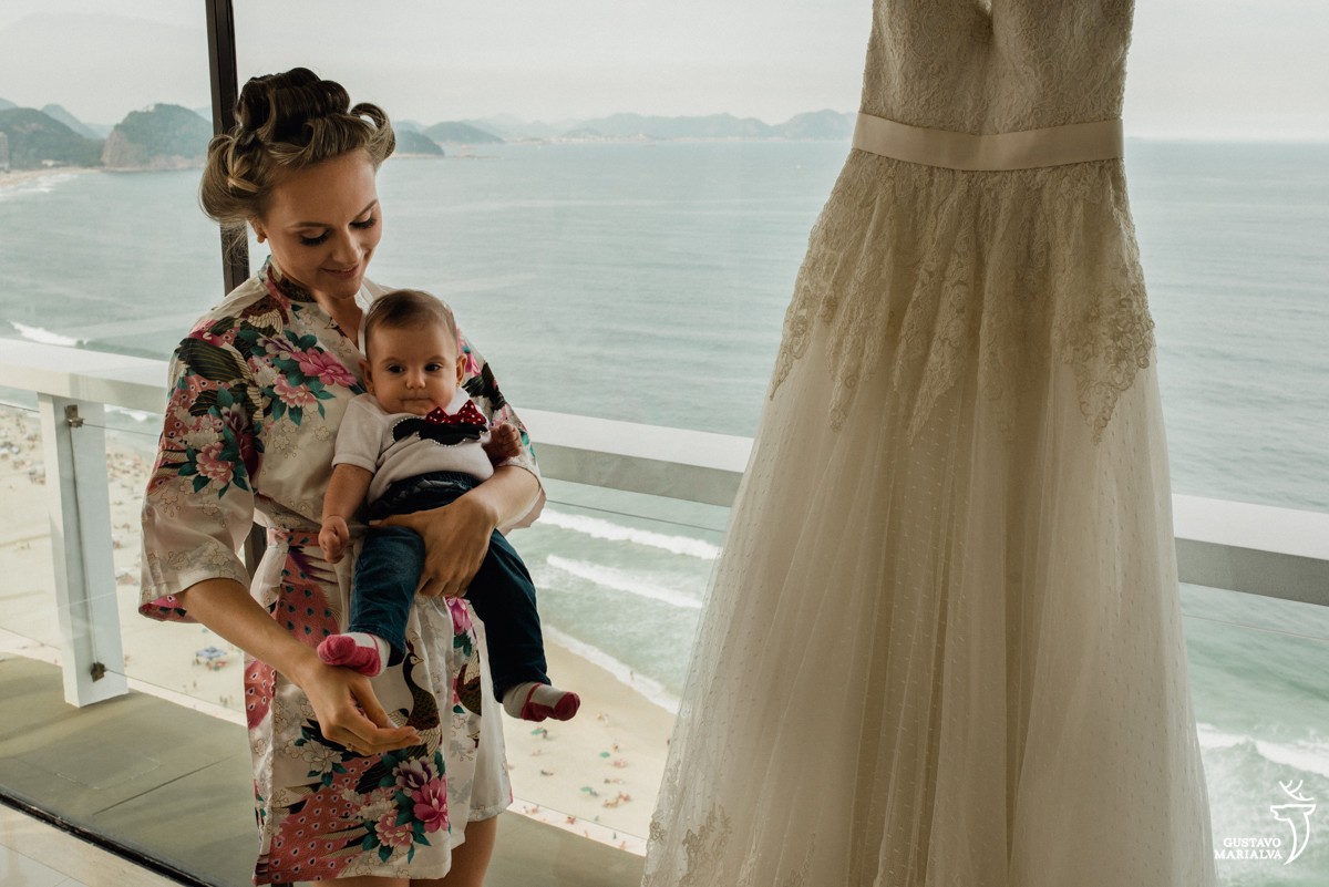 noiva segurando bebe no colo do lado do vestido de noiva com a praia de copacabana ao fundo no making do casamento no hotel rio othon palace