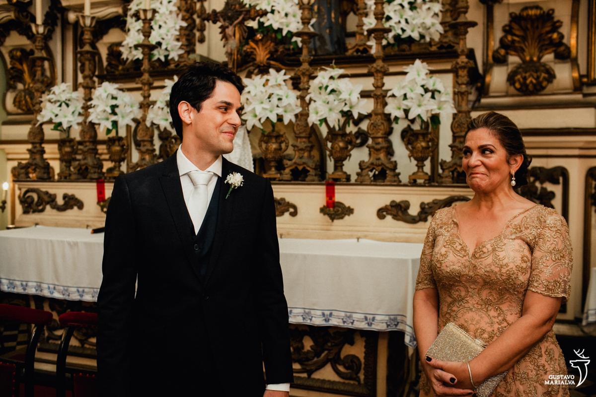 noivo olha sorrindo para mãe emocionada durante a cerimônia de casamento na igreja são josé