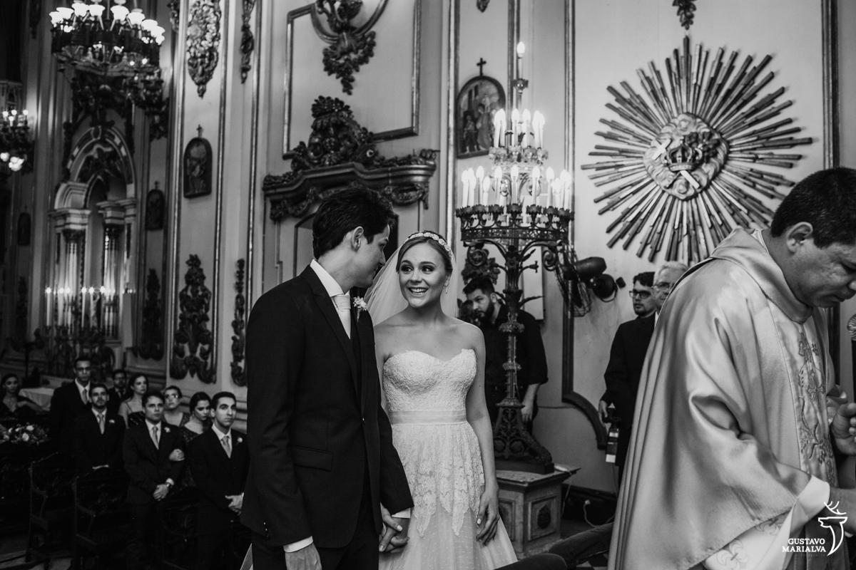 noiva olha sorrindo para o noivo durante a cerimônia de casamento na igreja são josé