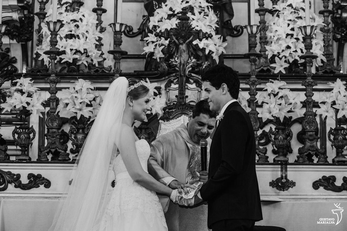 noivos seguram as mãos e se olham sorrindo durante a cerimônia de casamento na igreja são josé