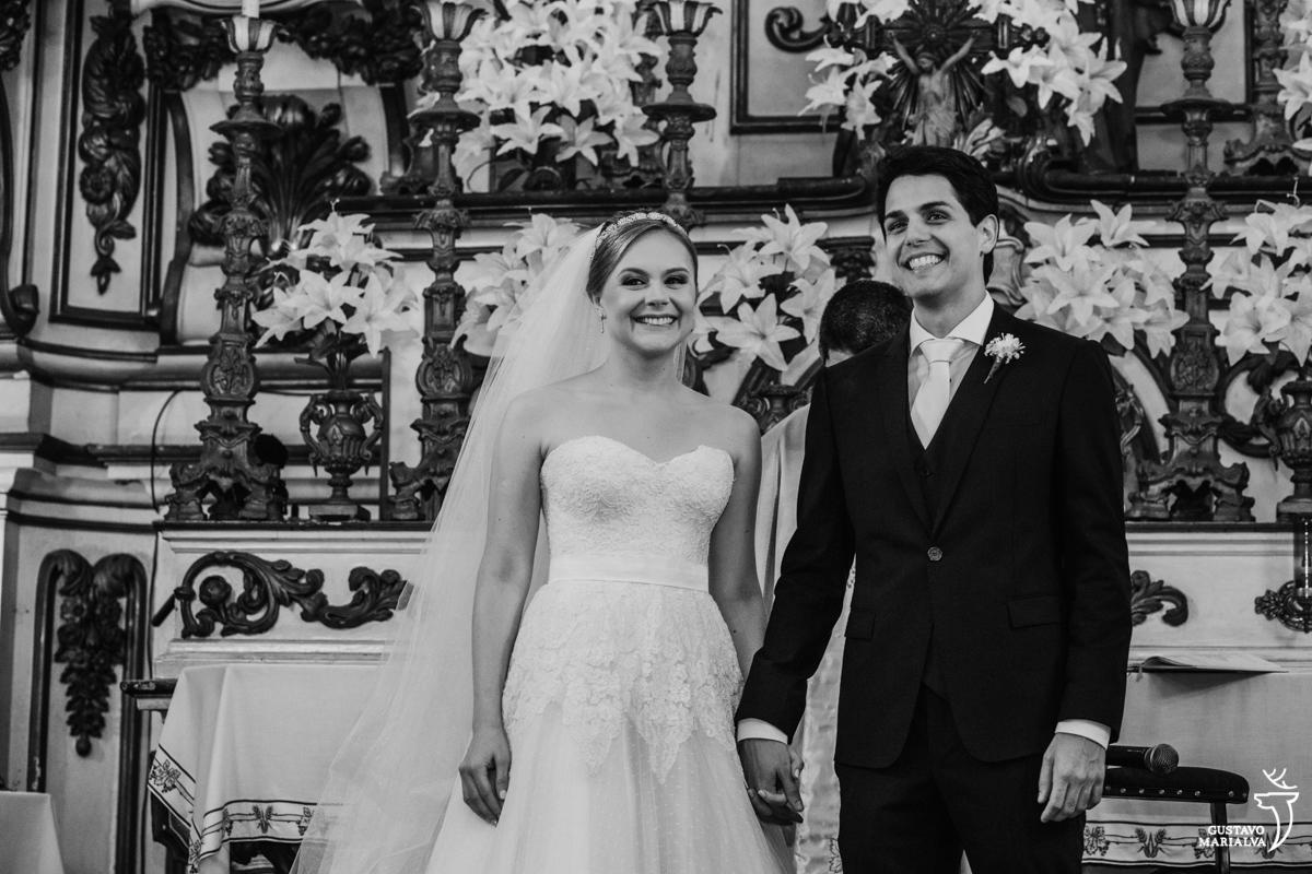 noivos sorriem emocionados e de mãos dadas durante a cerimônia de casamento na igreja são josé
