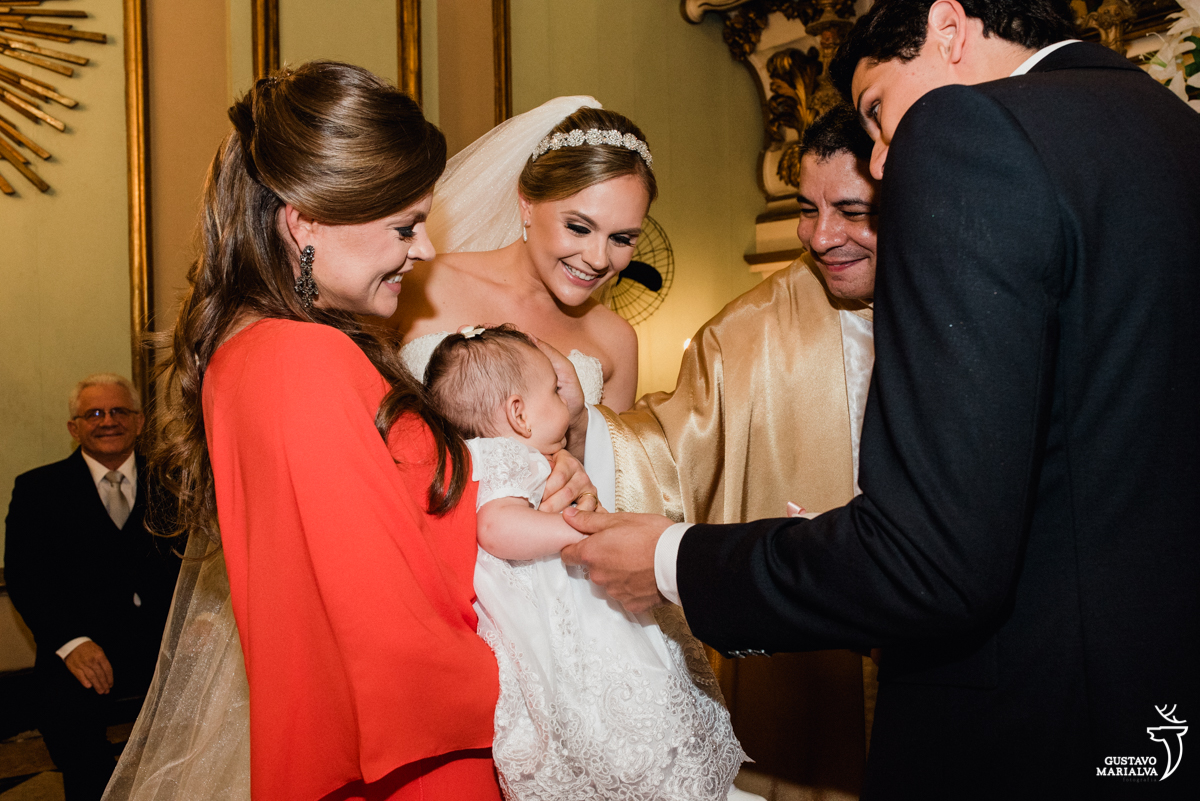 noiva emocionada recebe as alianças da irmã e da sobrinha durante a cerimônia de casamento na igreja são josé