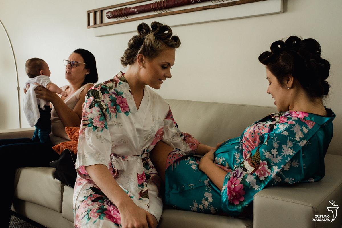 noiva passando a mão na barriga da madrinha grávida enquanto bebe brinca no fundo no making do casamento no hotel rio othon palace