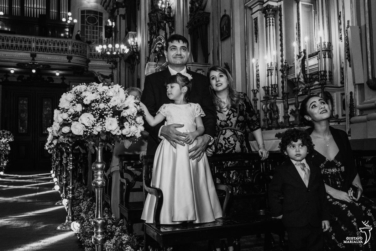 daminha brinca com as flores enquanto pajem e convidados observam a cerimônia de casamento na igreja são josé
