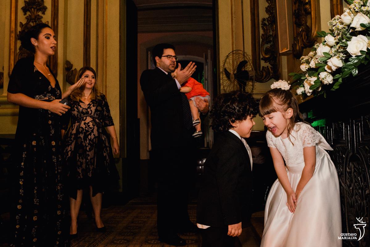 daminha e pajem brincam e convidados rezam ao fundo durante a cerimônia de casamento na igreja são josé