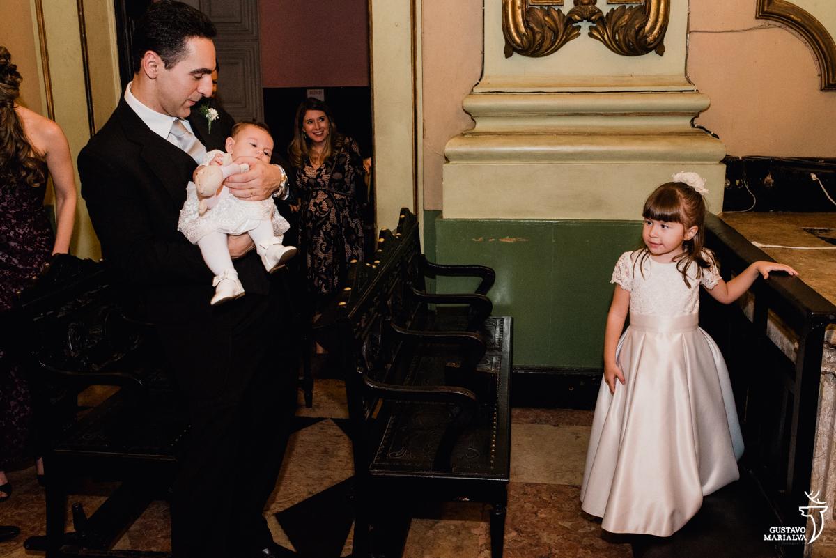 daminha observa bebê no colo do pai durante a cerimônia de casamento na igreja são josé