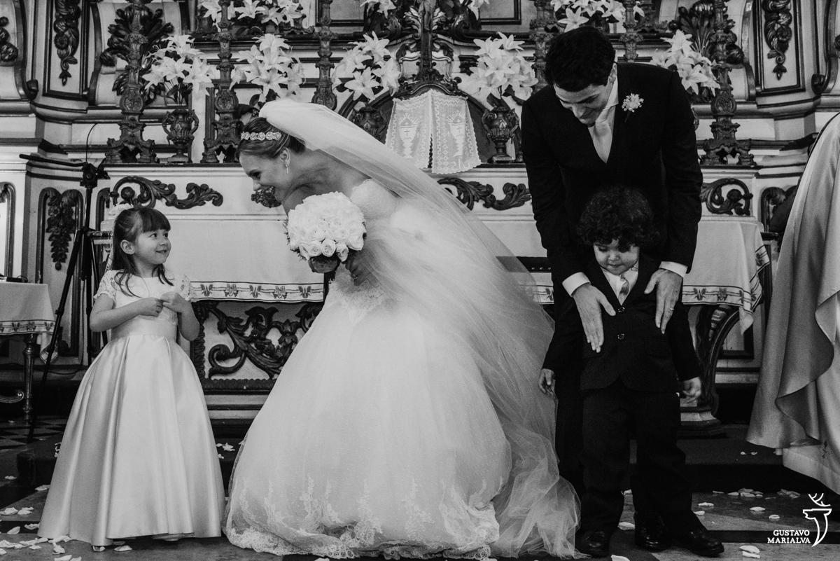 noiva brinca com a daminha enquanto o noivo abraça o pajem durante a cerimônia de casamento na igreja são josé