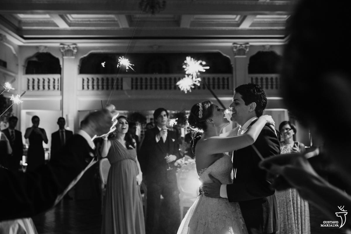 noivos dançando abraçados e sorridentes enquanto convidados seguram sparkles na festa de casamento na mansão botafogo