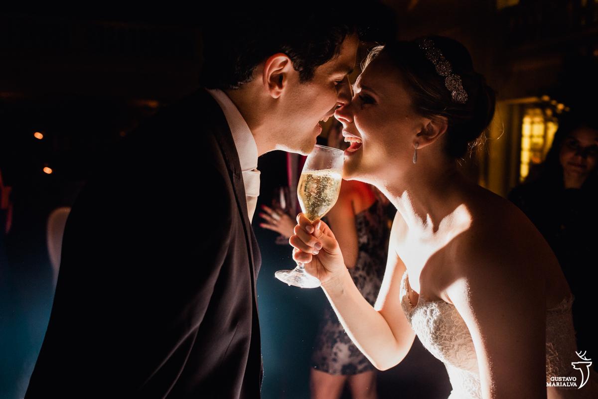 noivos cantam sorridentes com copo de espumante como microfone na festa de casamento na mansão botafogo
