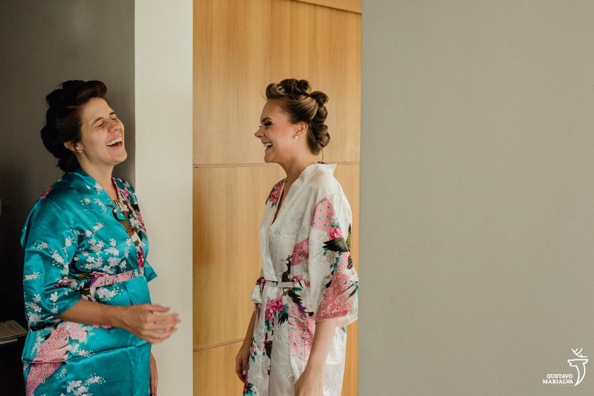 madrinha e noiva conversam sorrindo durante o making do casamento no hotel rio othon palace