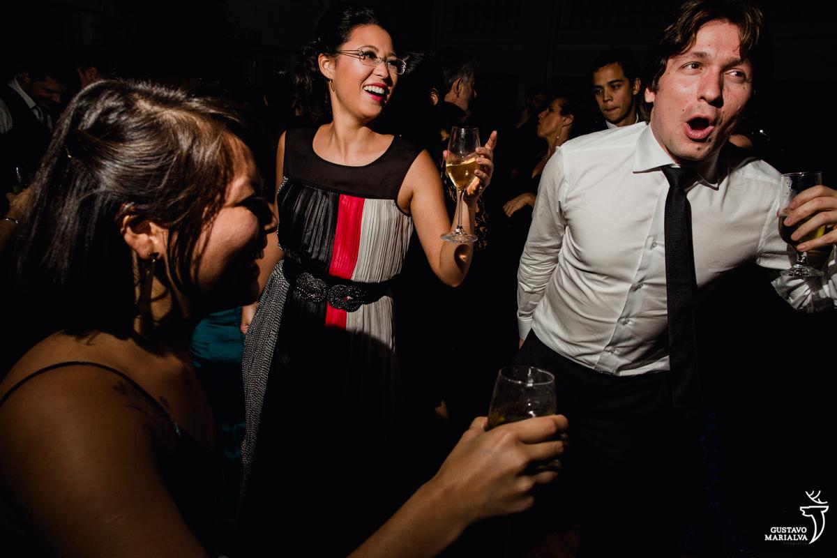 convidada cm taça de espumante na mão sorri enquanto convidado dança gritando e sorrindo