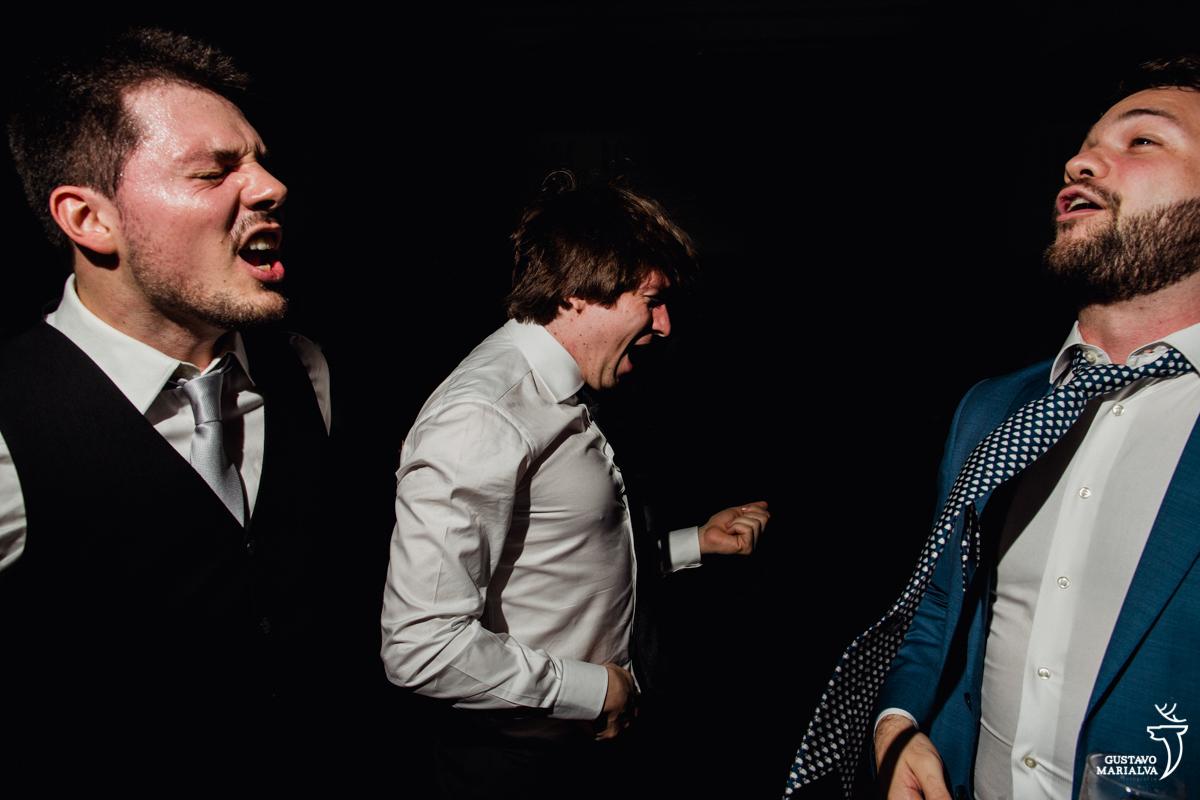 convidado faz air guitar enquanto outros dois convidados cantam animados na festa de casamento na mansão botafogo
