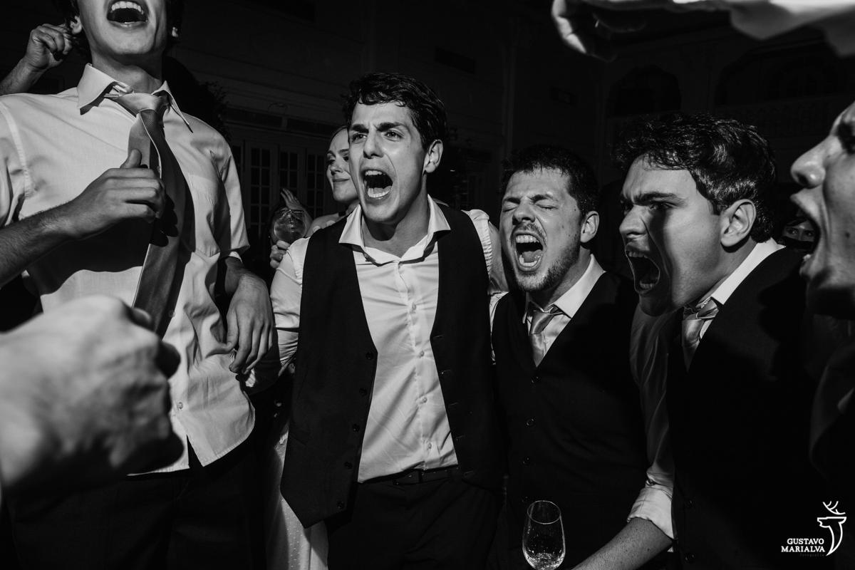noivo canta empolgado abraçado com os amigos e padrinhos na festa de casamento na mansão botafogo