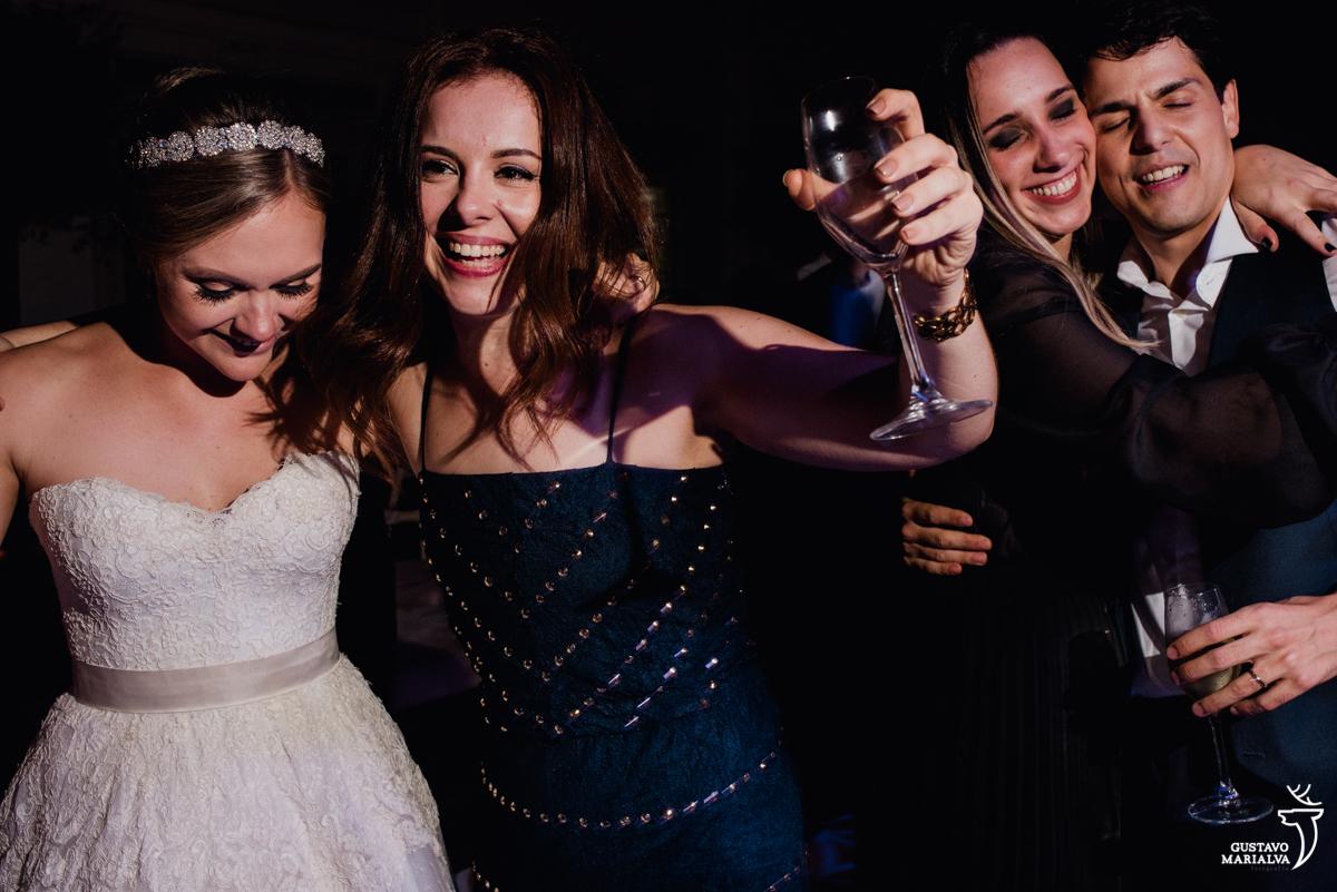noiva dança amiga segurando taça de espumante enquanto noivo abraça amiga emocionada