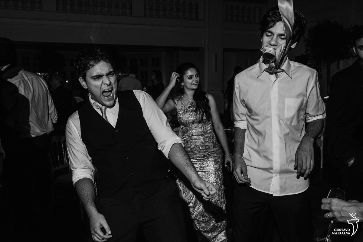 convidado grita dançando enquanto outro convidado pula com a gravata na cara
