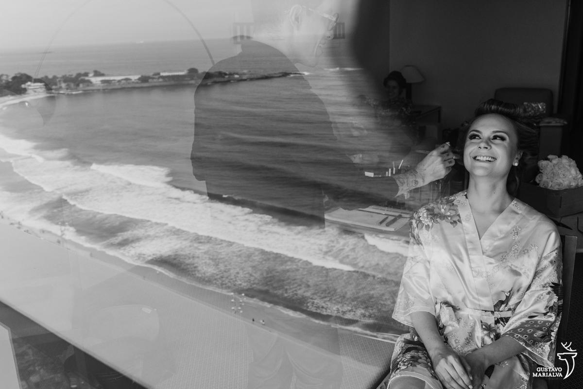 noiva sendo maquiada pelo maquiador eduardo jonata com a praia de copacabana no reflexo no making do casamento no hotel rio othon palace