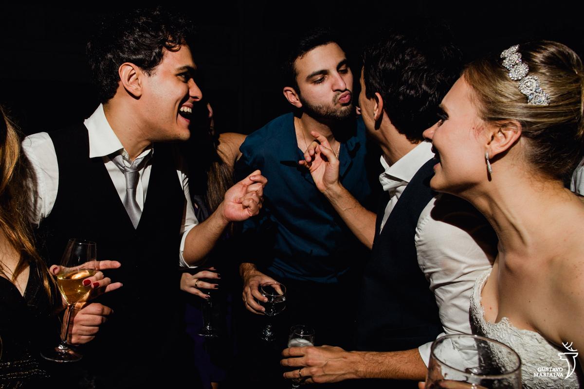 convidado finge dar um beijo no noivo enquanto noiva e amigos sorriem na festa de casamento na mansão botafogo