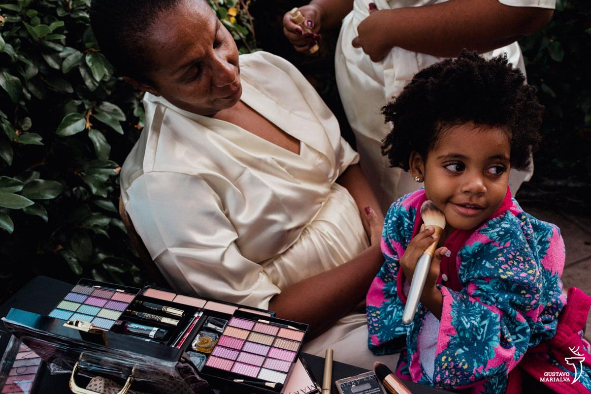 menina brincando de se maquiar enquanto é observada pela avó no making of do casamento no bosque da fazenda