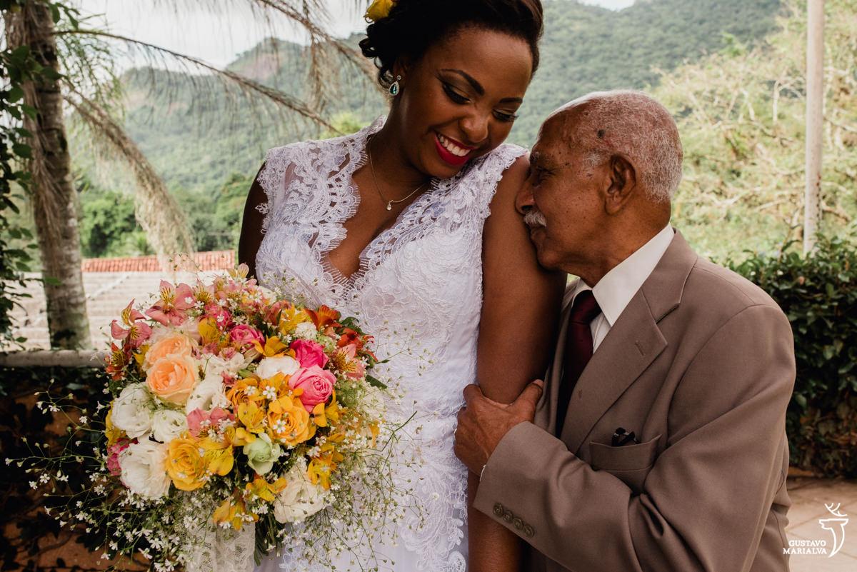 noiva sorri e abraça o avô emocionado segurando o buquê