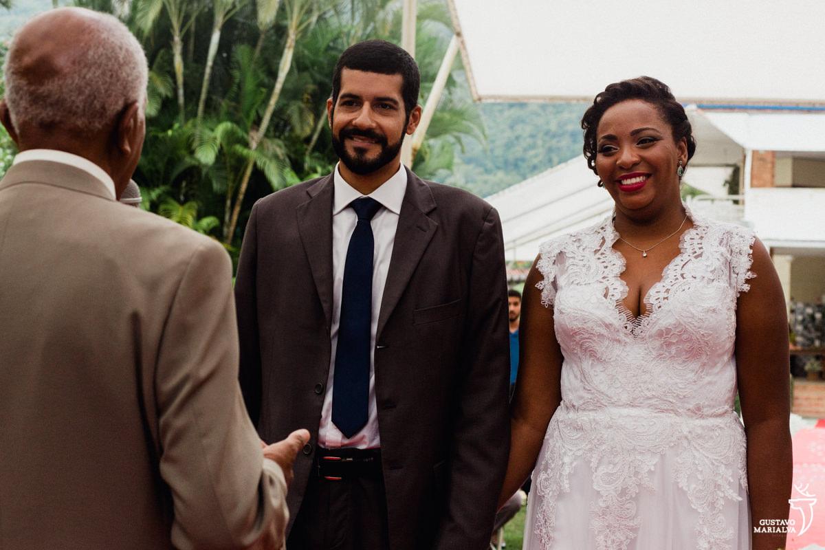 noivos sorriem com a cerimônia de casamento celebrada pelo avô