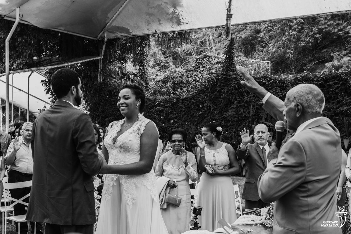 avô da noiva abençoa o casal com o braço estendido com a noiva sorrindo e mãe da noiva emocionada no fundo