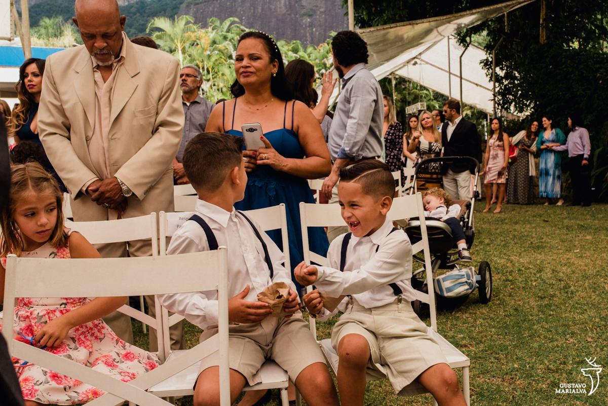 criança sorri e brinca com amigo durante a cerimônia de casamento
