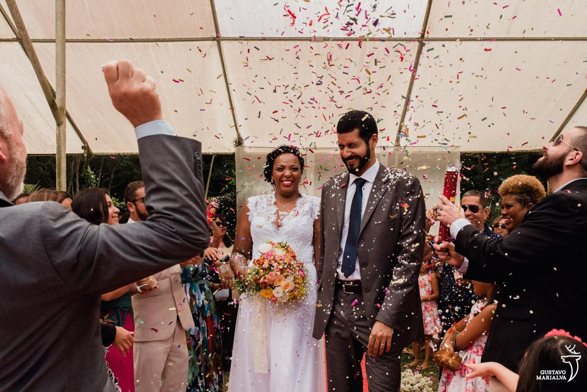 noivos saem da cerimônia sorrindo enquanto convidados jogam confete e serpentina